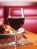A glass of red wine in front of a dish of food