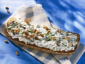 Soft cheese, pine nuts and mint on slice of toast