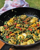 Potato tortilla with peppers and spinach in a frying pan