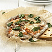 Tomato, anchovy and cheese pizza on baking parchment