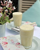 Coconut, banana and mango smoothie in two glasses