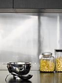 Pasta in jars, stainless steel colander and spoon