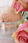 A scoop of rose ice cream in a glass dish with pink roses