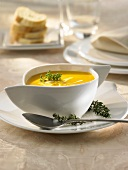 Pumpkin soup with sour cream and thyme in a soup cup