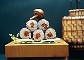 Five tuna maki, stacked on a wooden board