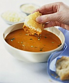 Man dipping white bread into a bowl of tomato soup