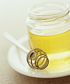 Jar of honey with a honey dipper