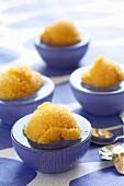 Orange sorbet in four glass bowls
