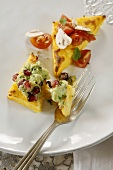 Polenta slices topped with avocado cream and tomatoes