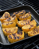 Pieces of pumpkin in a grill frying pan on a grill