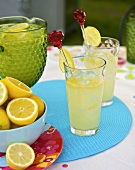 Lemonade with ice cubes in glasses out of doors