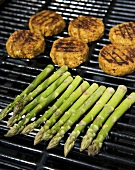 Chick-pea burgers and green asparagus on a grill