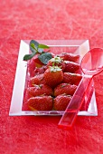 Strawberry and orange salad with mint in a glass dish