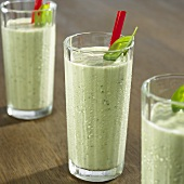 Cold cucumber and basil soup in three glasses with straws