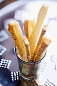 Puff pastry straws with Parmesan and cumin in a glass