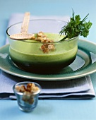 Cucumber and herb soup with croutons in a glass bowl