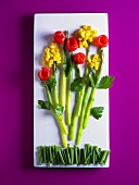 Vegetable salad arranged in the shape of flowers on a platter