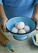 Woman holding a colander half-full of eggs in her hands