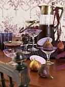 Verschiedene lilafarbene Getränke, Trauben und Feigen