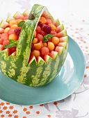 Watermelon basket filled with melon balls and raspberries
