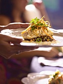Woman serving grouper on lentils with vegetables