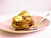 Stack of pancakes with banana slices and honey