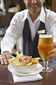 Lobster poutine with a glass of beer on a counter (Canada)