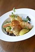 Deep-fried prawns in tempura batter on salad leaves