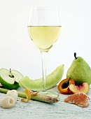 Glass of white wine surrounded by various fruits (aromas)