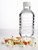 Assorted tablets in front of a bottle of water
