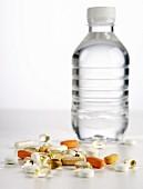 Verschiedene Tabletten vor einer Wasserflasche