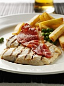 Grilled chicken breast with bacon, peas and chips