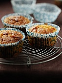 Three muffins in paper cases on a cake rack