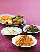 Assorted Middle Eastern appetisers on four plates
