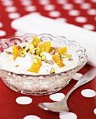 Yoghurt with orange segments & pistachios in a glass bowl