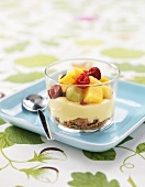 Crushed biscuits, custard and fruit in a glass
