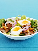 Salad leaves with bacon, chanterelles and boiled egg