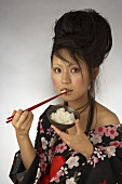 A Japanese woman eating rice out of a bowl