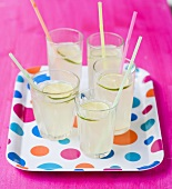 Five glasses of lemonade with straws on spotted tray