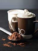 Two cups of espresso with whipped cream and cocoa powder
