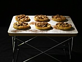 Six small nut tarts on an occasional table