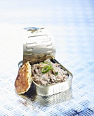 Sardine salad in a tin with a potato pancake