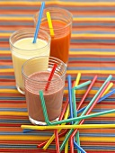 Three different fruit cocktails with coloured straws