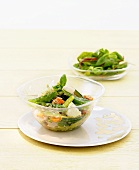 Vegetable salad with Parmesan in a glass bowl