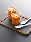 Curried tomato soup in two glass cups on a slate board