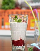 A glass of banana milkshake on raspberry puree