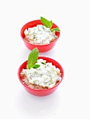 Two bowls of raita (cucumber salad with yoghurt) with mint