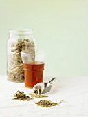 A glass of tea with various medicinal herbs