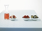 Three different antipasti in dishes with rosé wine