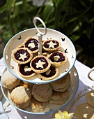 Jam tarts and scones on a tiered stand out of doors